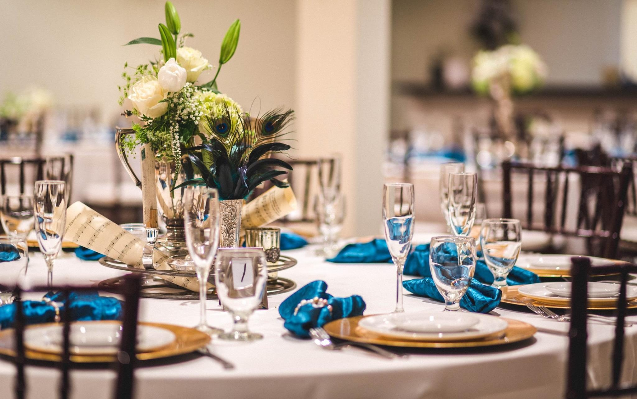A table setting for a wedding, featuring a white tablecloth and blue napkins.