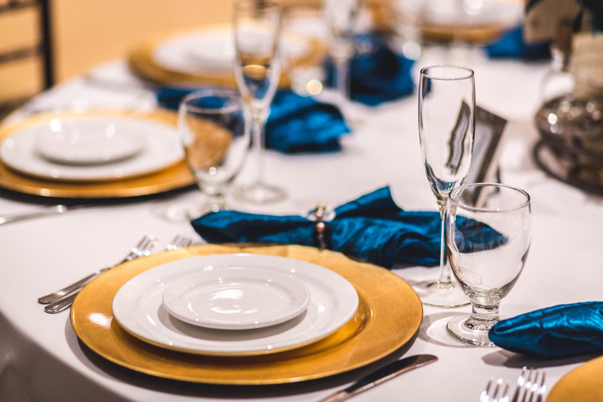 A wedding reception place setting, featuring ivory colored china and blue napkins