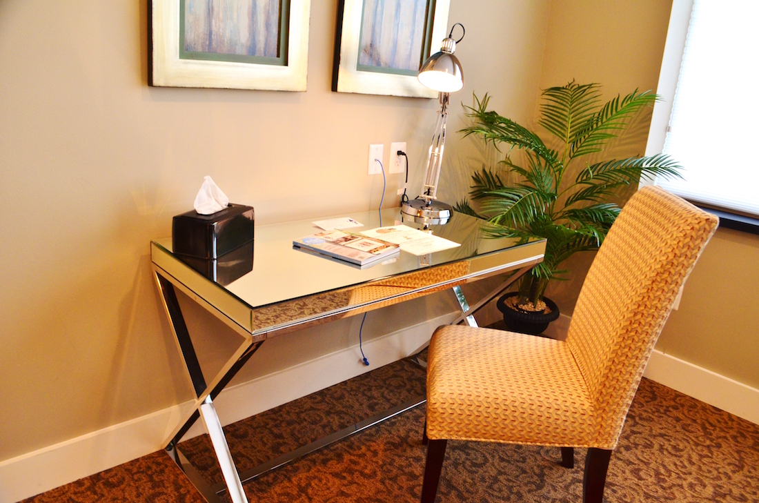 This is a photo showing a wooden desk and a chair in the Luxury Suite of the Culpeper Center.